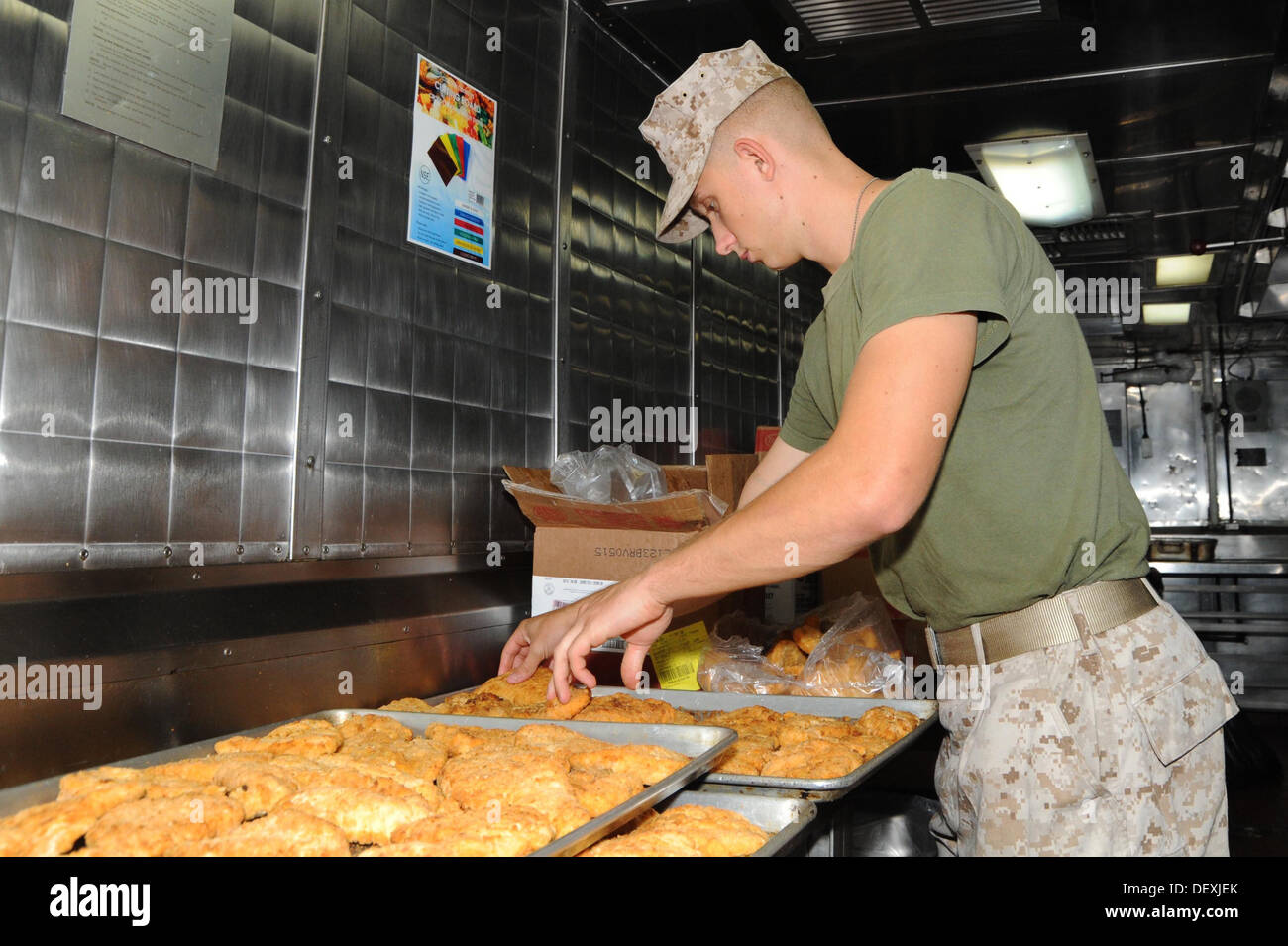 Pfc. Stephen Guardalabene helps prepare meals in USS Bataan's galley Sept. 18. Guardalabene is attached to the 22nd Marine Expeditionary Unit currently integrating on Bataan as part of PHIBRON-MEU Integrated Training (PMIT). PMIT allows sailors and Marine - Stock Image