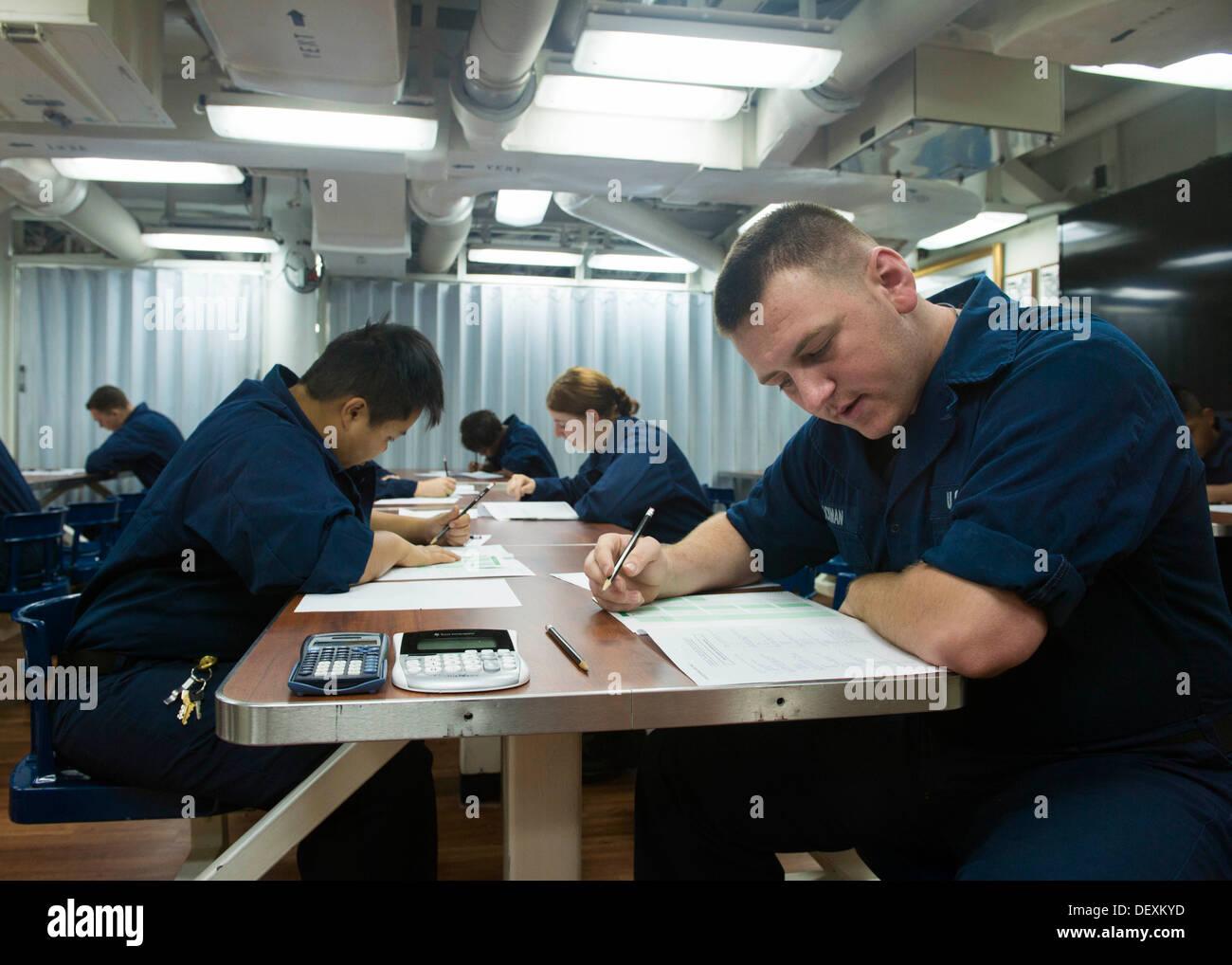 Sailors take various petty officer 3rd class advancement exams aboard the guided missile destroyer USS Mustin (DDG 89). Mustin is on patrol with the George Washington Carrier Strike Group in the U.S. 7th fleet area of responsibility supporting security an - Stock Image