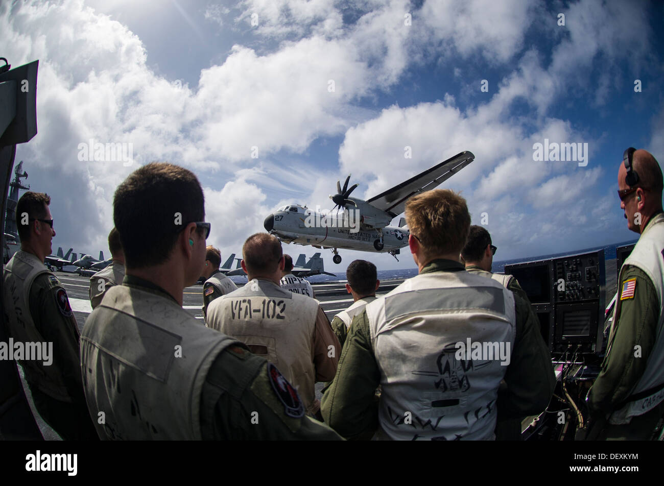 Landing safety officers observe a C-2A Greyhound from the Providers of Fleet Logistics Squadron (VRC) 30, Detachment 5, as it p - Stock Image