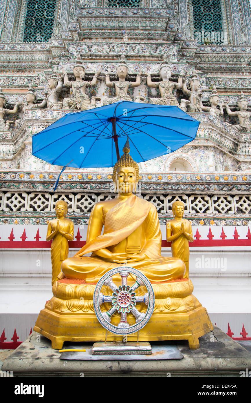 three gold Buddha Statues under blue umbrella Bangkok Thailand Wad Arun temple - Stock Image