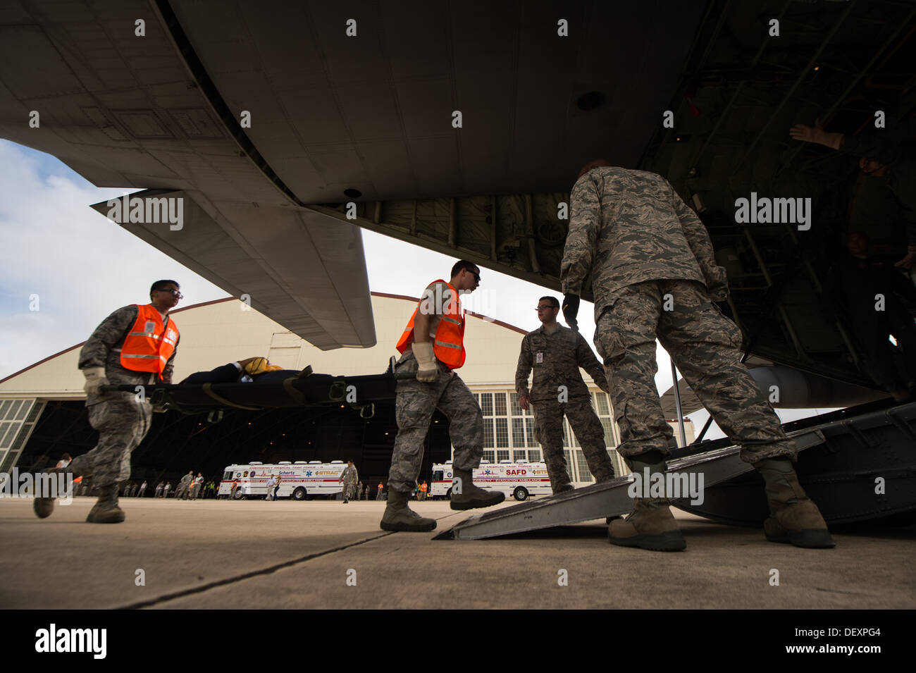 Airmen carry a patient onto a WC-130J Hurricane Hunter while participating in the annual San Antonio Mass Casualty Exercise Event at Joint Base San Antonio-Lackland, Texas, Sept. 19, 2013. The SAMCEE 13 was a complex disaster scenario designed to test the - Stock Image