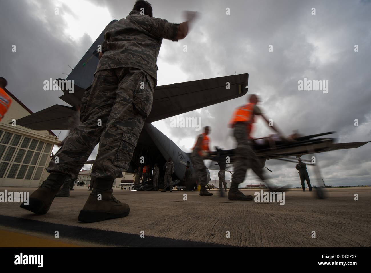 Airmen transport a patient from a WC-130J Hurricane Hunter to an ambulance while participating in the annual San Antonio Mass Casualty Exercise Event at Joint Base San Antonio-Lackland, Texas, Sept. 19, 2013. The SAMCEE 13 was a complex disaster scenario - Stock Image