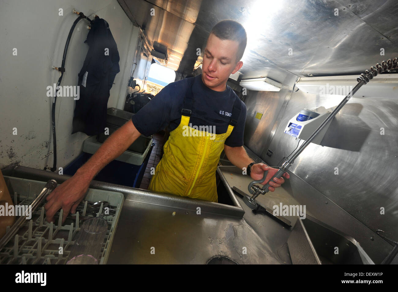 Officer Candidate Tripp Haas washes dishes in the scullery aboard the Coast Guard Barque Eagle on Wednesday, Sept. 11, 2013. Trainees aboard the Eagle cycle through numerous ship positions to develop a deeper understanding of what it takes to operate a Co - Stock Image