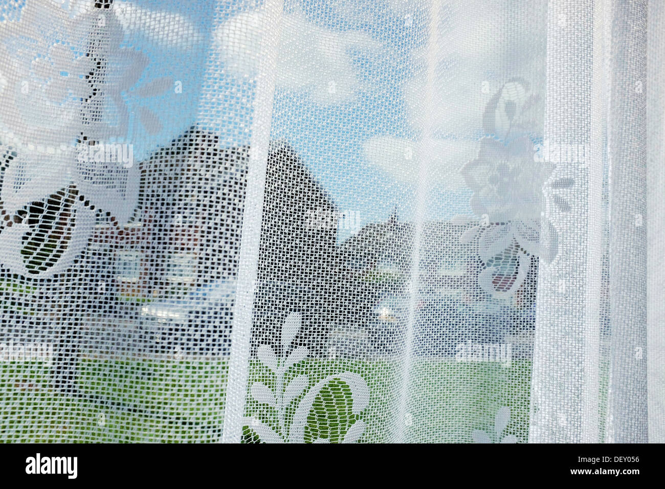 Suburban scene through net curtains. - Stock Image