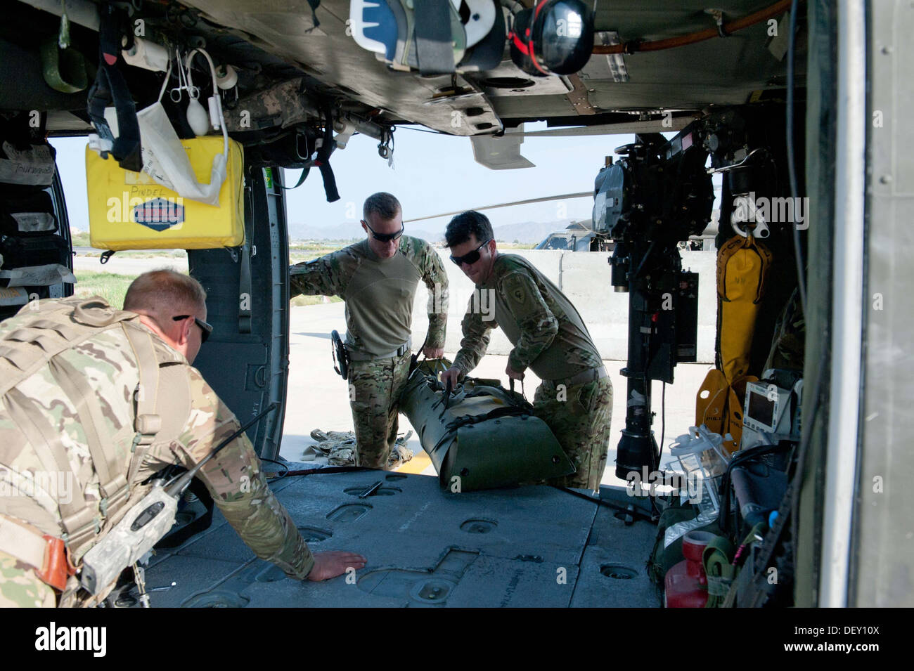 U.S. Army Spc. Trevor Milbury, center, a crew chief, and Sgt. Aaron DeAnglis, right, a standardization instructor, both with the - Stock Image