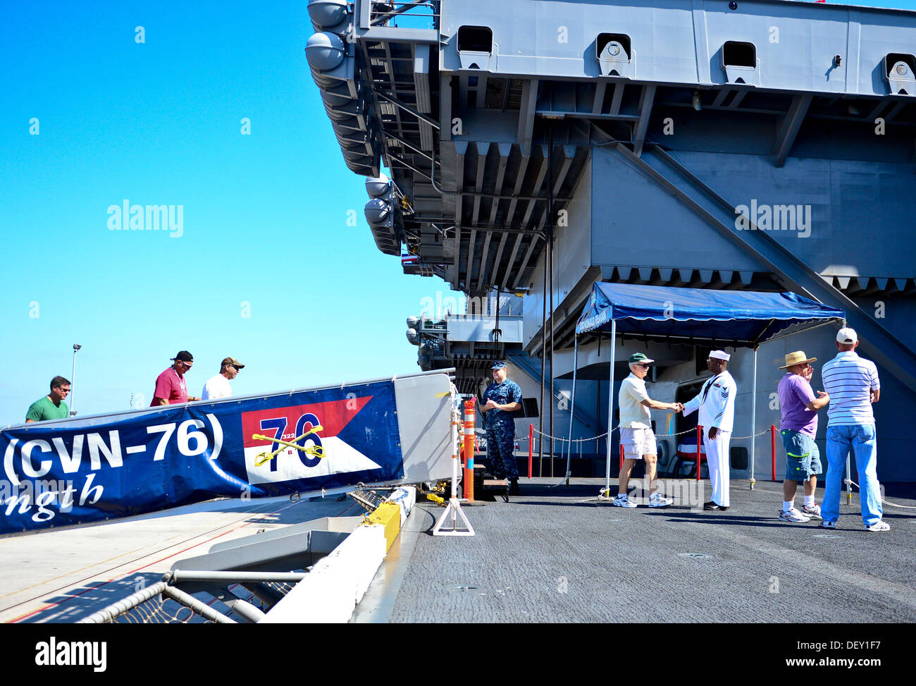 Guests walk aboard the aircraft carrier USS Ronald Reagan (CVN 76) for a tour. Ronald Reagan, 'America's Flagship,' is participating in the annual Coronado Speed Festival. This event was created in 1997, to honor the military while enjoying a rich automob - Stock Image
