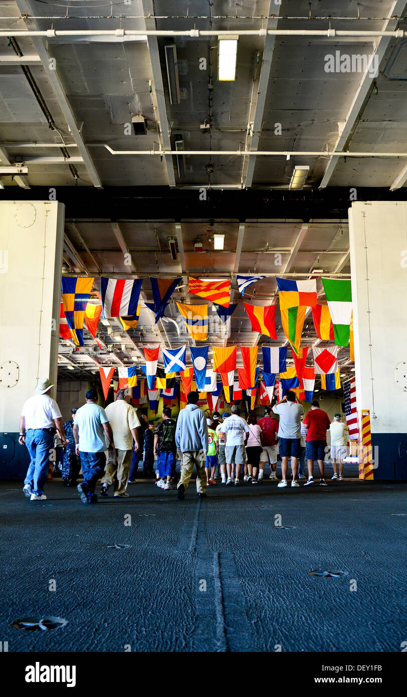 Guests walks into the hangar bay aboard the aircraft carrier USS Ronald Reagan (CVN 76) during a tour. Ronald Reagan, 'America's Flagship,' is participating in the annual Coronado Speed Festival. This event was created in 1997, to honor the military while - Stock Image