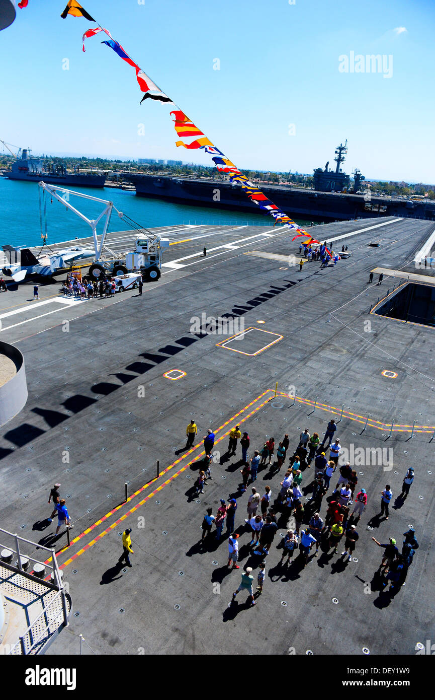 """Guests tour the flight deck of the aircraft carrier USS Ronald Reagan (CVN 76) during a tour. Ronald Reagan, """"America's Flagship,"""" is participating in the annual Coronado Speed Festival. This event was created in 1997, to honor the military while enjoying - Stock Image"""