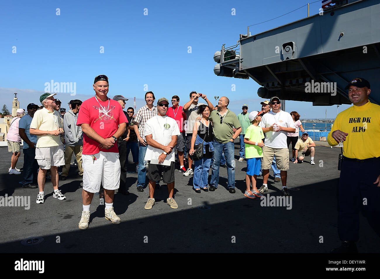 "Guests ride an aircraft elevator to the flight deck aboard the aircraft carrier USS Ronald Reagan (CVN 76) during a tour. Ronald Reagan, ""America's Flagship,"" is participating in the annual Coronado Speed Festival. This event was created in 1997, to honor - Stock Image"