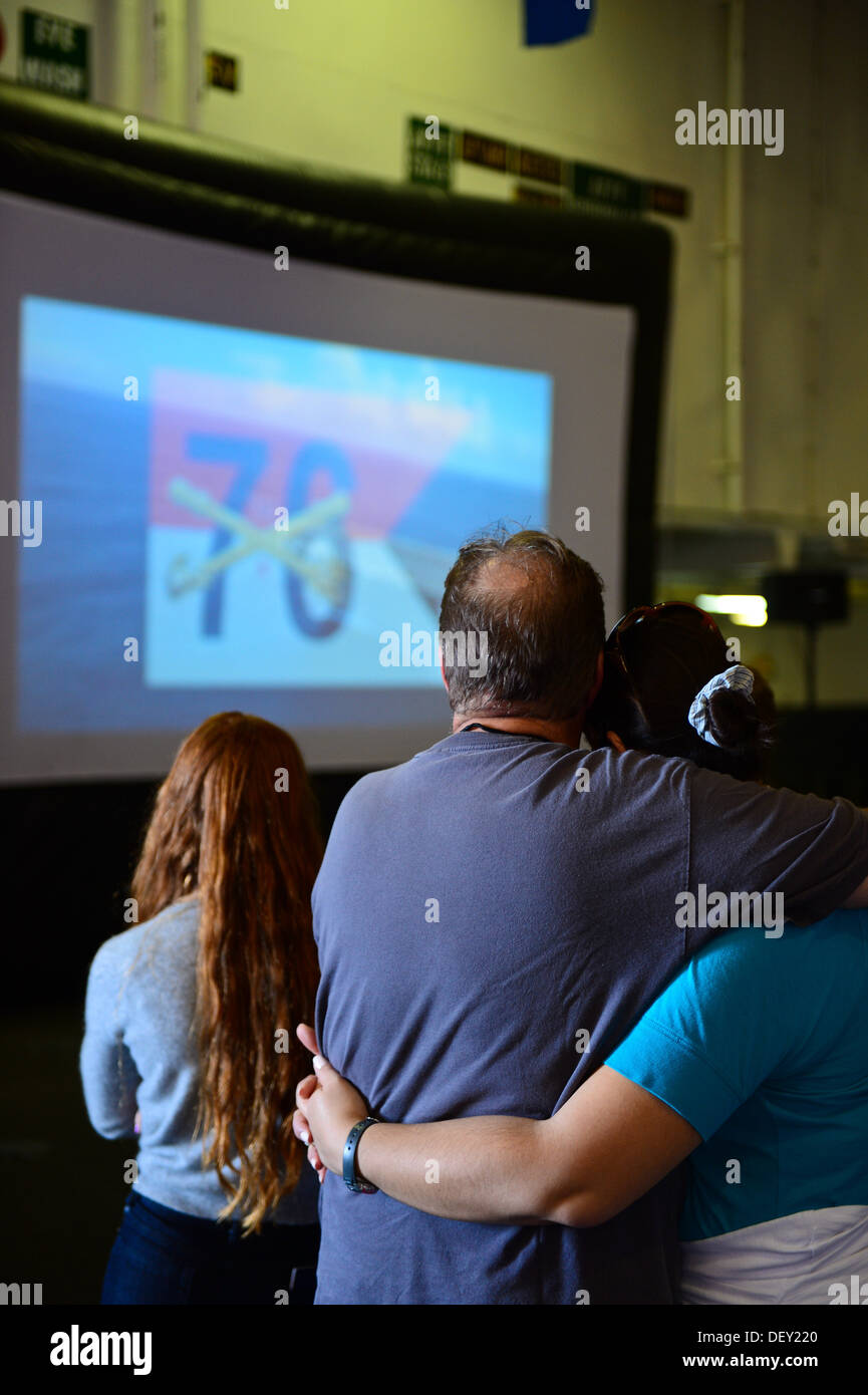 "Guests watch a video presentation displaying the aircraft carrier USS Ronald Reagan's (CVN 76) recent operations during a tour in the ship's hangar bay. Ronald Reagan, ""America's Flagship,"" is participating in the annual Coronado Speed Festival. This even - Stock Image"