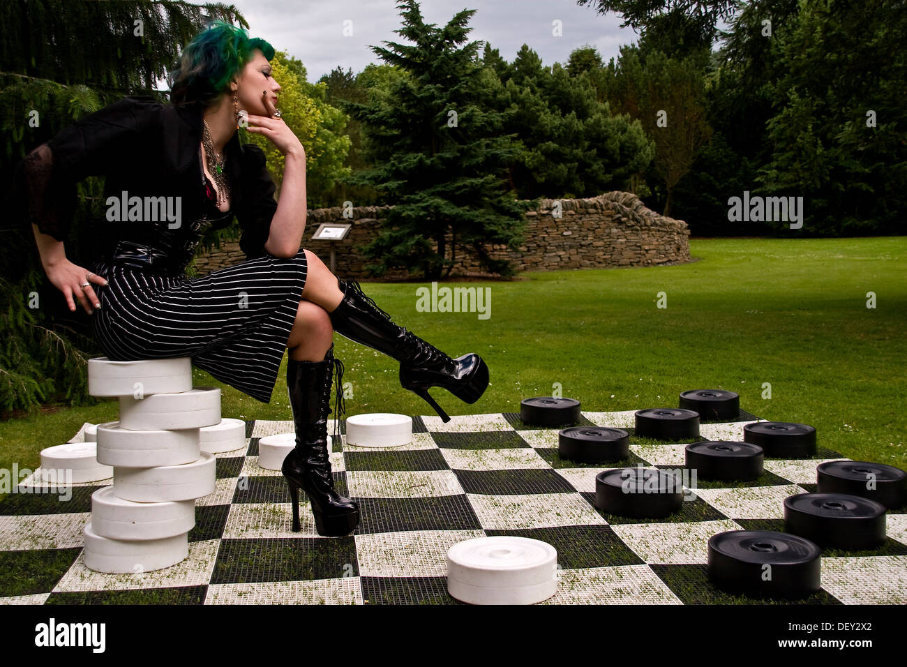 Woman wearing an Alice In Wonderland style outfit sitting on a pile of white checkers inside the Dundee Botanic Stock Photo