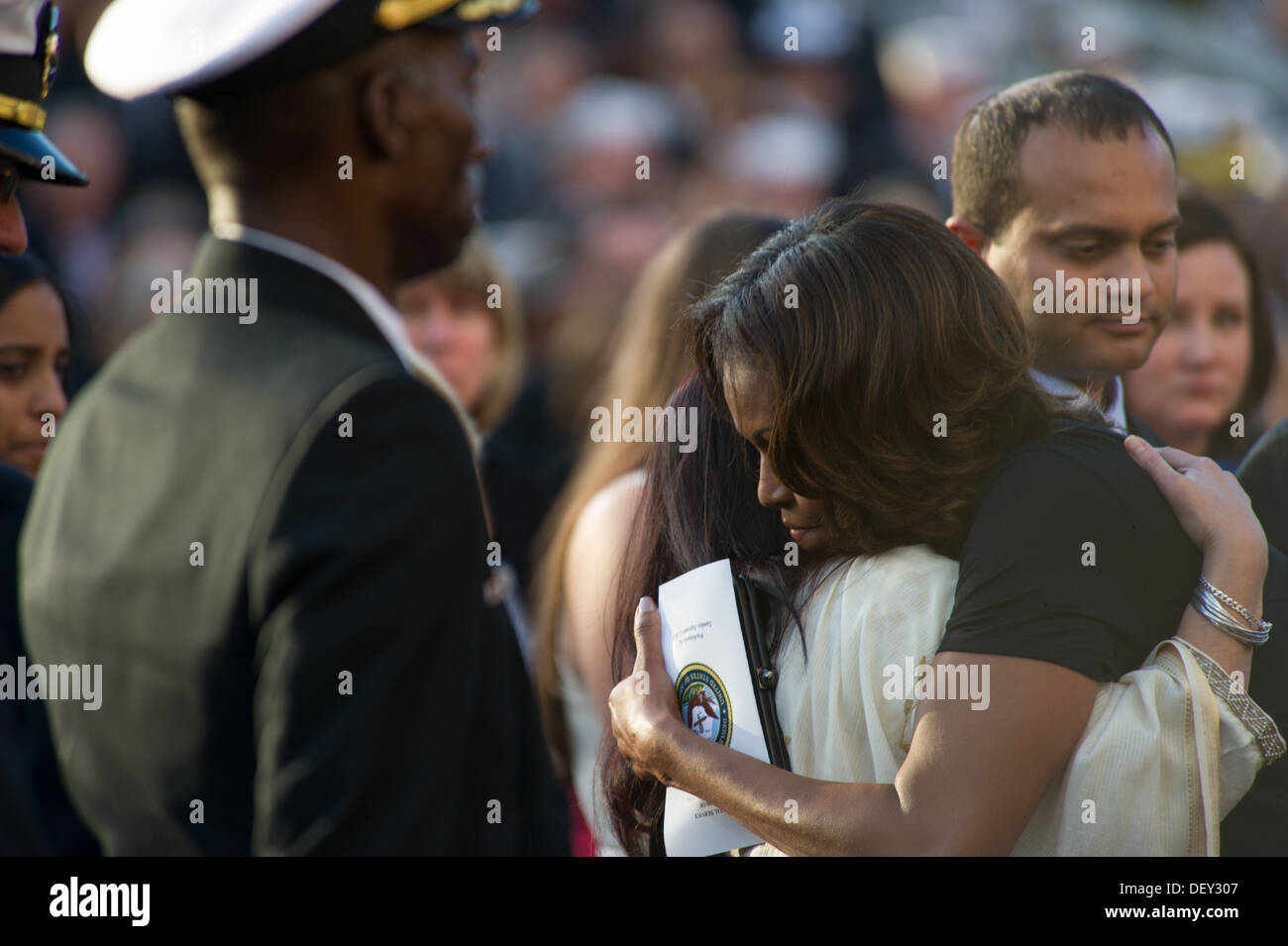 U.S. First Lady Michelle Obama hugs friends and family of those killed during a Navy Yard shooting at a memorial Stock Photo