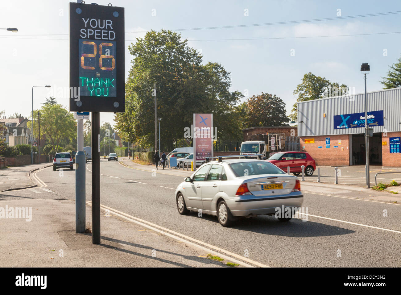 Car within the speed limit as it passes a traffic speed warning indicator, Nottinghamshire, England, UK - Stock Image