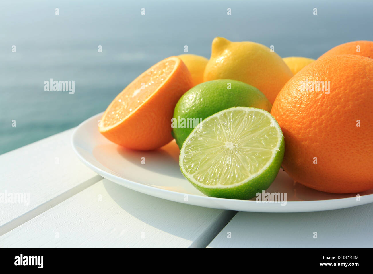 Oranges, lemons and limes by the coast - Stock Image