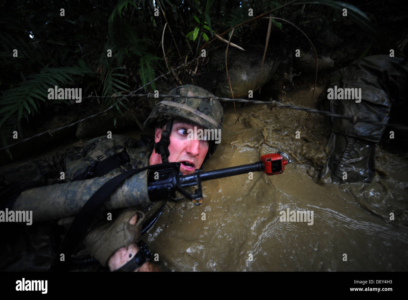 Naval Mobile Construction Battalion (NMCB) 3 Construction Mechanic 2nd Class Christopher Allen crawls under barbwire and through - Stock Image