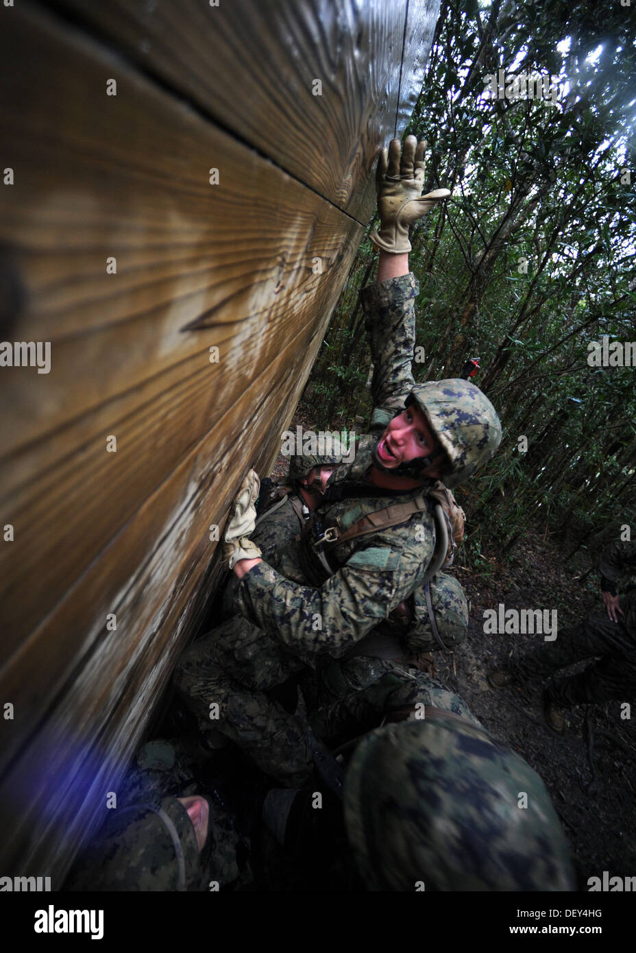 Naval Mobile Construction Battalion (NMCB) 3 Construction Mechanic 3rd Class Nicholas Edwards lunges off his squad members to re - Stock Image