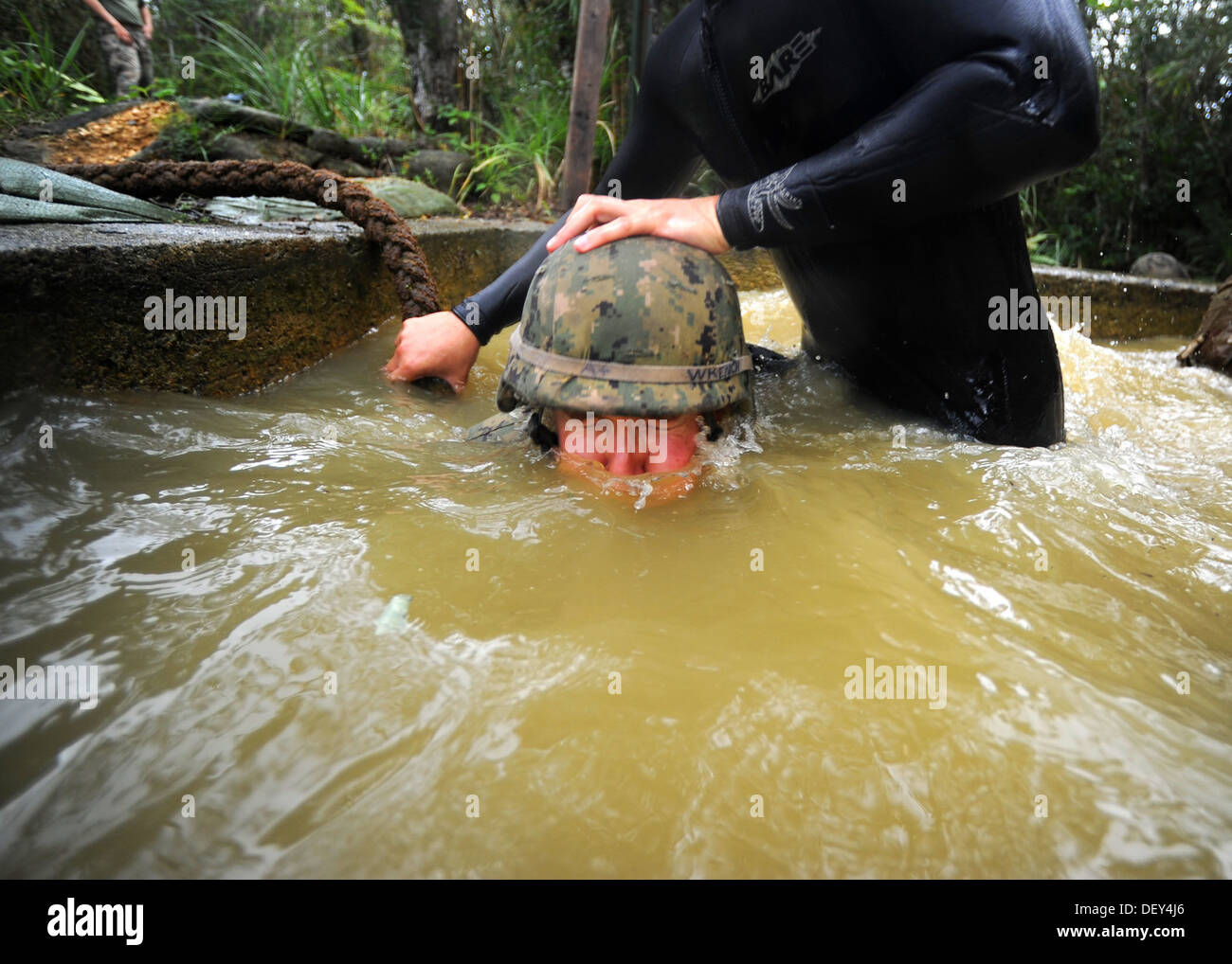 A Marine Corps Jungle Warfare Training Center (JWTC) Instructor helps Naval Mobile Construction Battalion (NMCB) 3 Construction - Stock Image