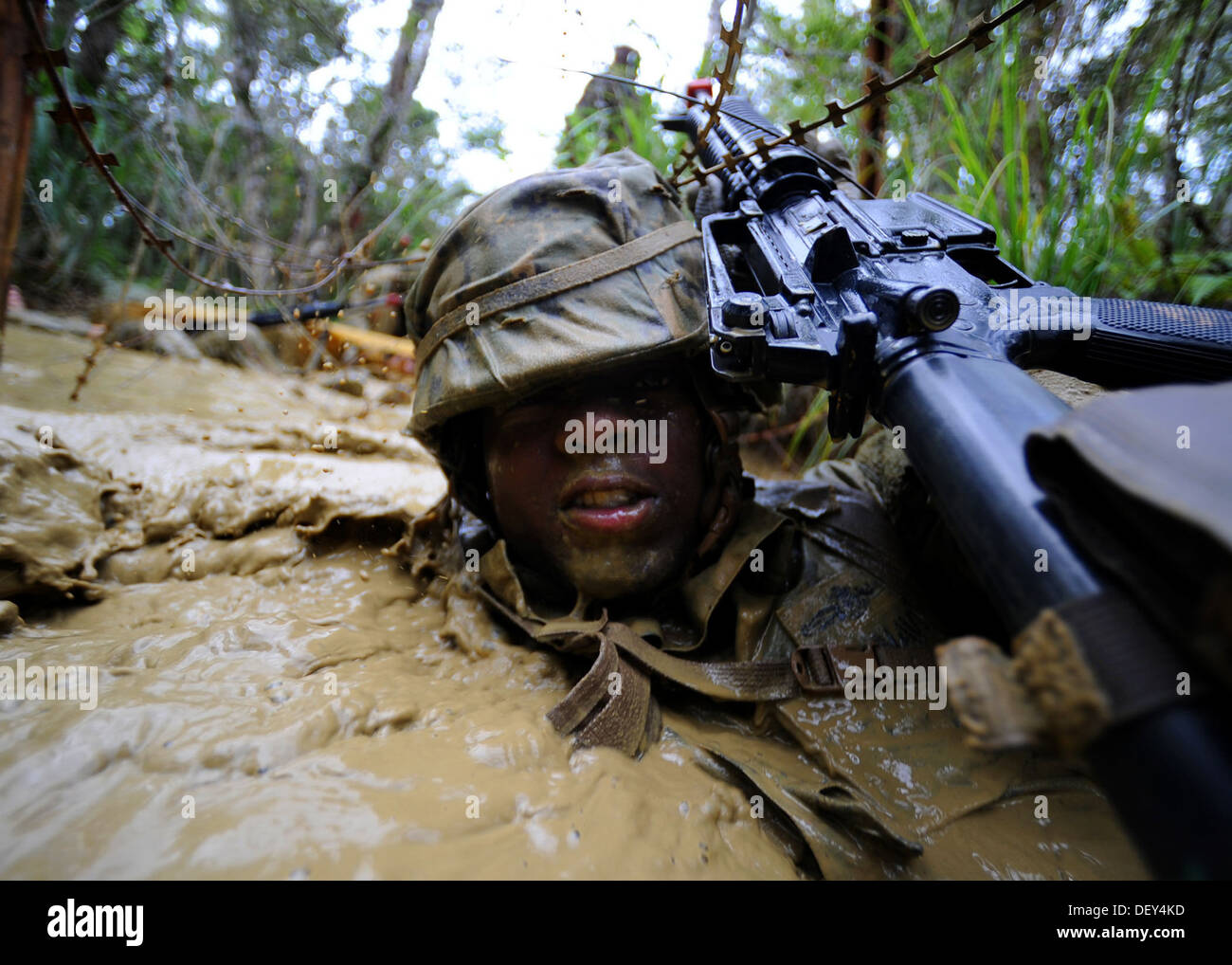 Naval Mobile Construction Battalion (NMCB) 3 Construction Electrician 2nd Class Dwayne Watson uses his weapon to push Constantin - Stock Image