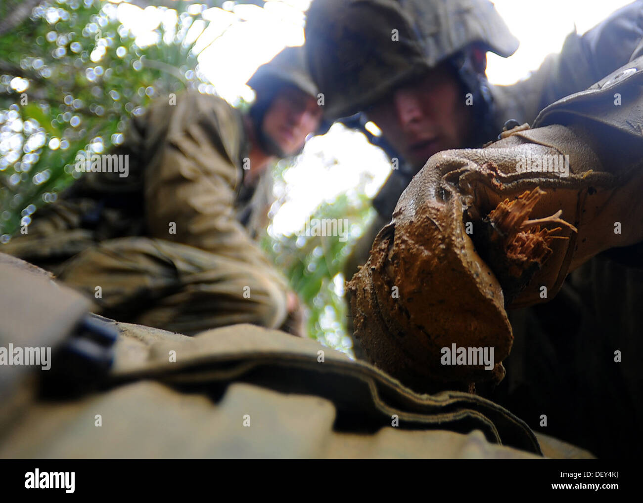 Seabees from Naval Mobile Construction Battalion (NMCB) 3 construct an improvised tourniquet using a broken stick and a belt wh - Stock Image