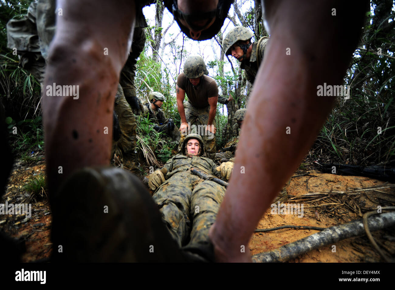 Seabees from Naval Mobile Construction Battalion (NMCB) 3 carry a mock casualty on an improvised stretcher through a tiny crevic - Stock Image