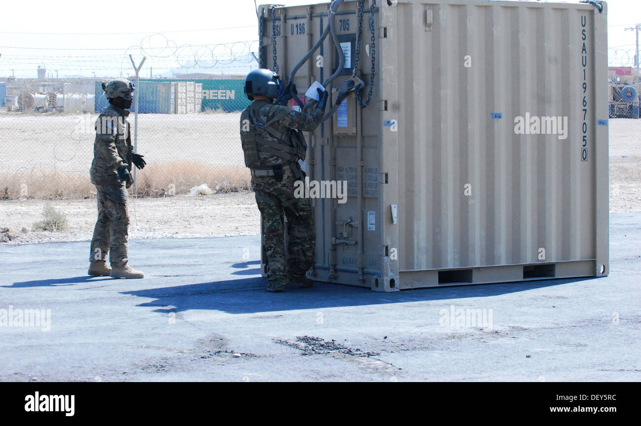 U.S. Army Sgt. Dan Glenn, right, inspects a container to be sling loaded prior to a personnel and equipment movement mission at - Stock Image