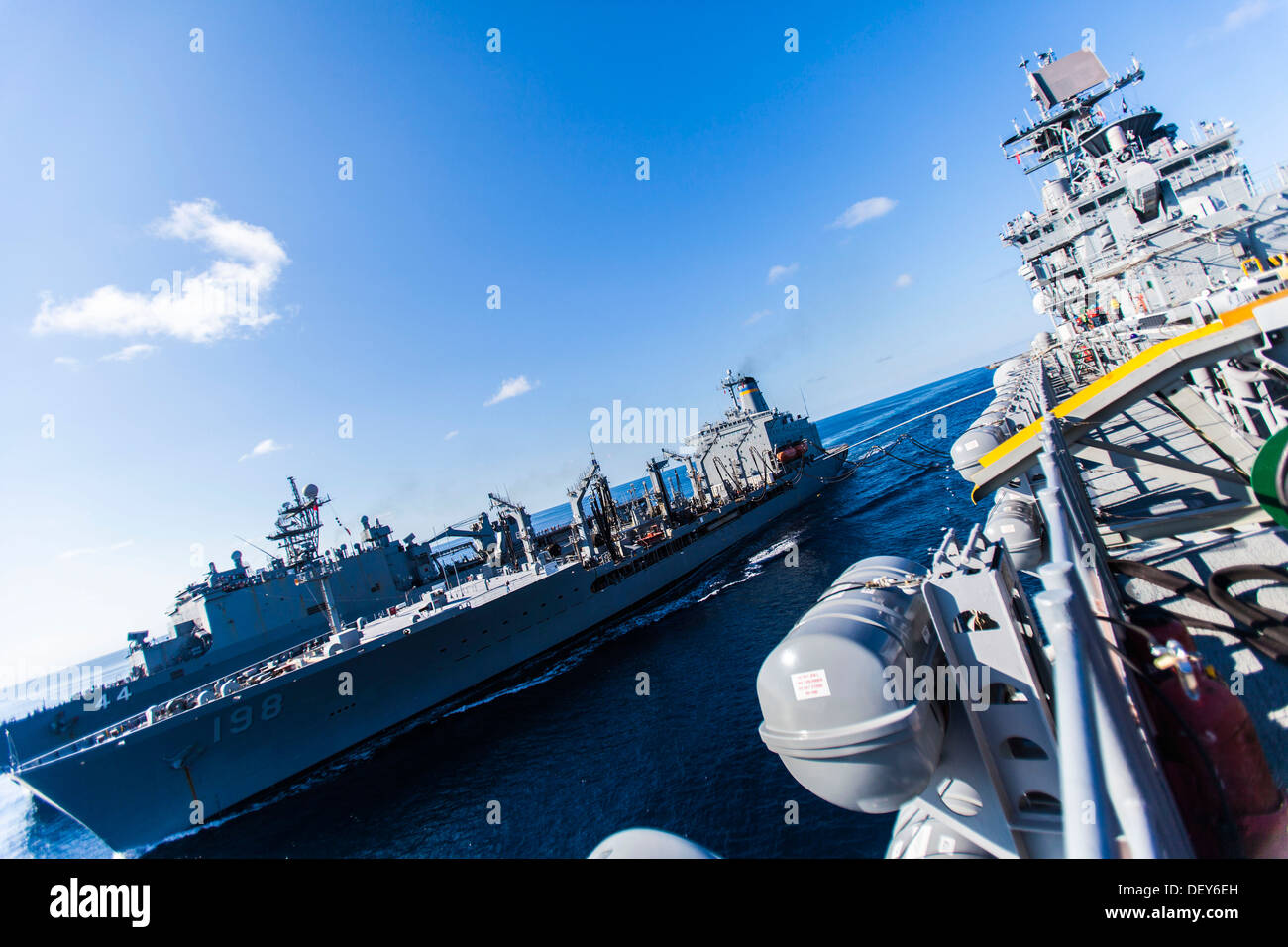 The fleet replenishment oiler USNS Big Horn (T-AOE 198), left, conducts a replenishment-at-sea with the amphibious assault ship - Stock Image