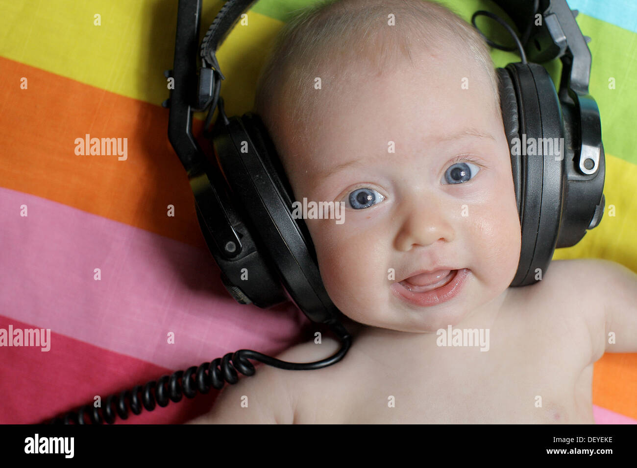 Baby girl listening/listens to music on headphones. Baby wearing headphones. - Stock Image