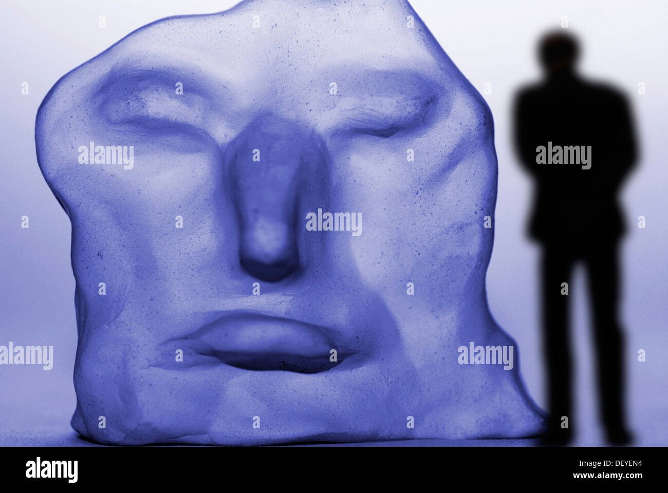 Lonely man in front of a distorted face, depression - Stock Image
