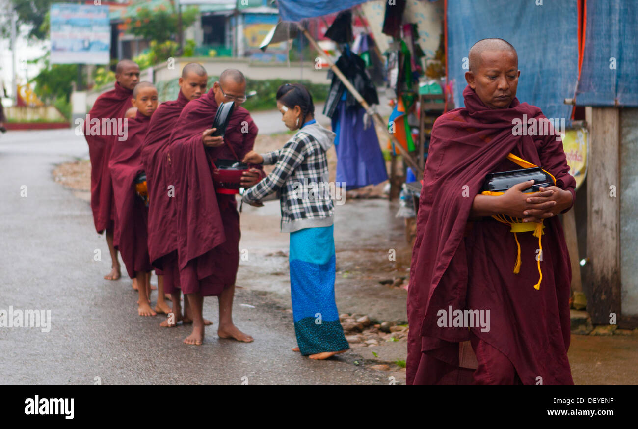 Monks receive morning alms in downtown Kinpun, Burma. - Stock Image