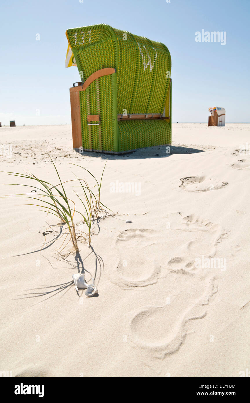 Green beach chair and footprints in the sand, Nebel, Amrum, Amrum, North Frisian Islands, Schleswig-Holstein, Germany - Stock Image