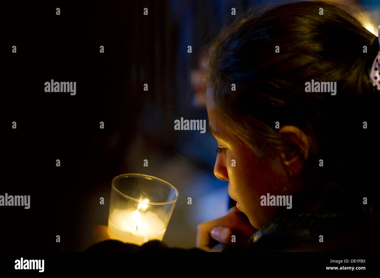 Girl with candle, in prayer, Germany - Stock Image