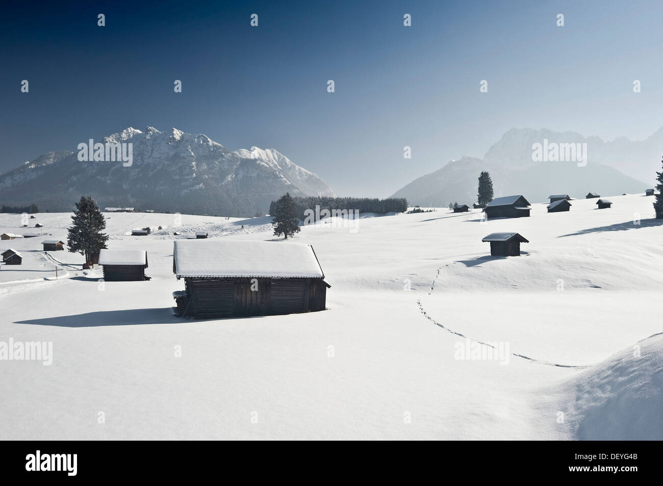 Snow-covered pastures and hay barns, Wetterstein range at back, Mittenwald, Upper Bavaria, Bavaria, Germany - Stock Image
