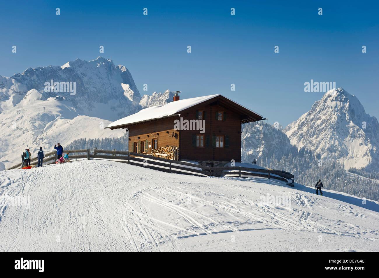 Wooden house on a snow-covered hill, Mt Alpspitze and Mt Zugspitze at back, Eckbauer, Garmisch-Partenkirchen, Upper Stock Photo
