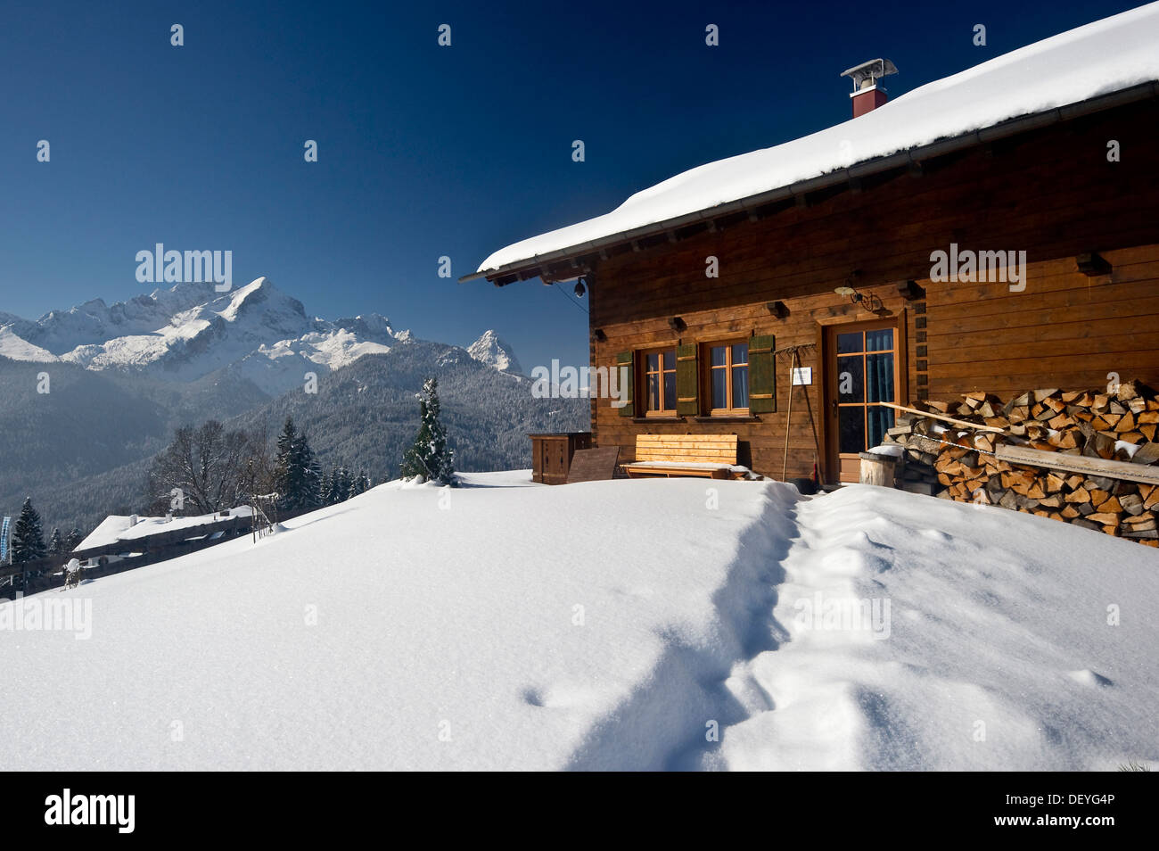 Wooden house on a snow-covered hill, Mt Alpspitze and Mt Zugspitze at back, Eckbauer, Garmisch-Partenkirchen, Upper Stock Photo
