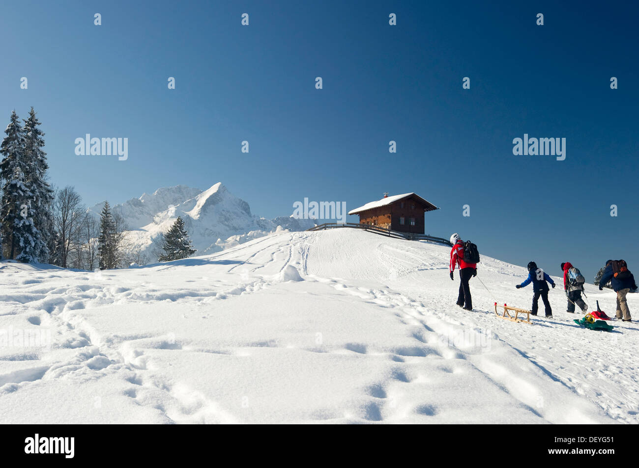 Sledgers and a wooden house on a snow-covered hill, Mt Alpspitze and Mt Zugspitze at back, Eckbauer, Garmisch-Partenkirchen Stock Photo