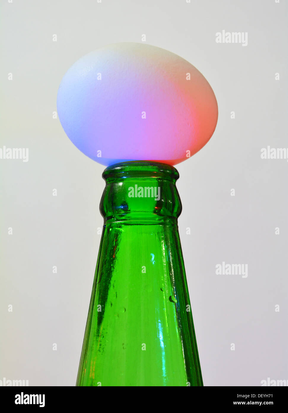 Egg balanced on beer bottle - Stock Image