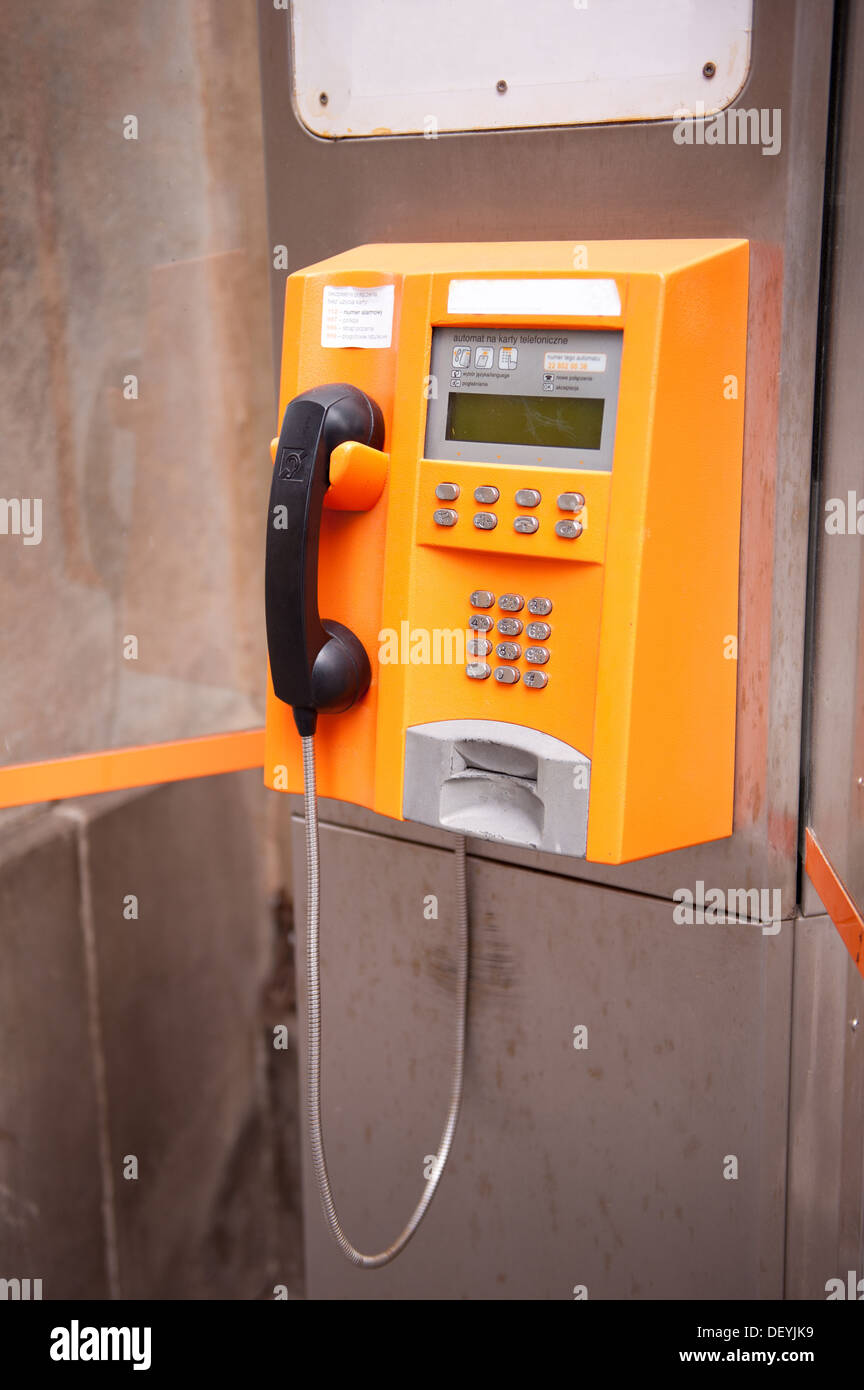 Old yellow telephone kiosk and black handset - Stock Image