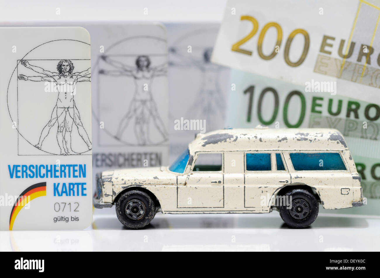 Health insurance cards and miniature ambulance, symbolic image for financial difficulties of health insurances - Stock Image