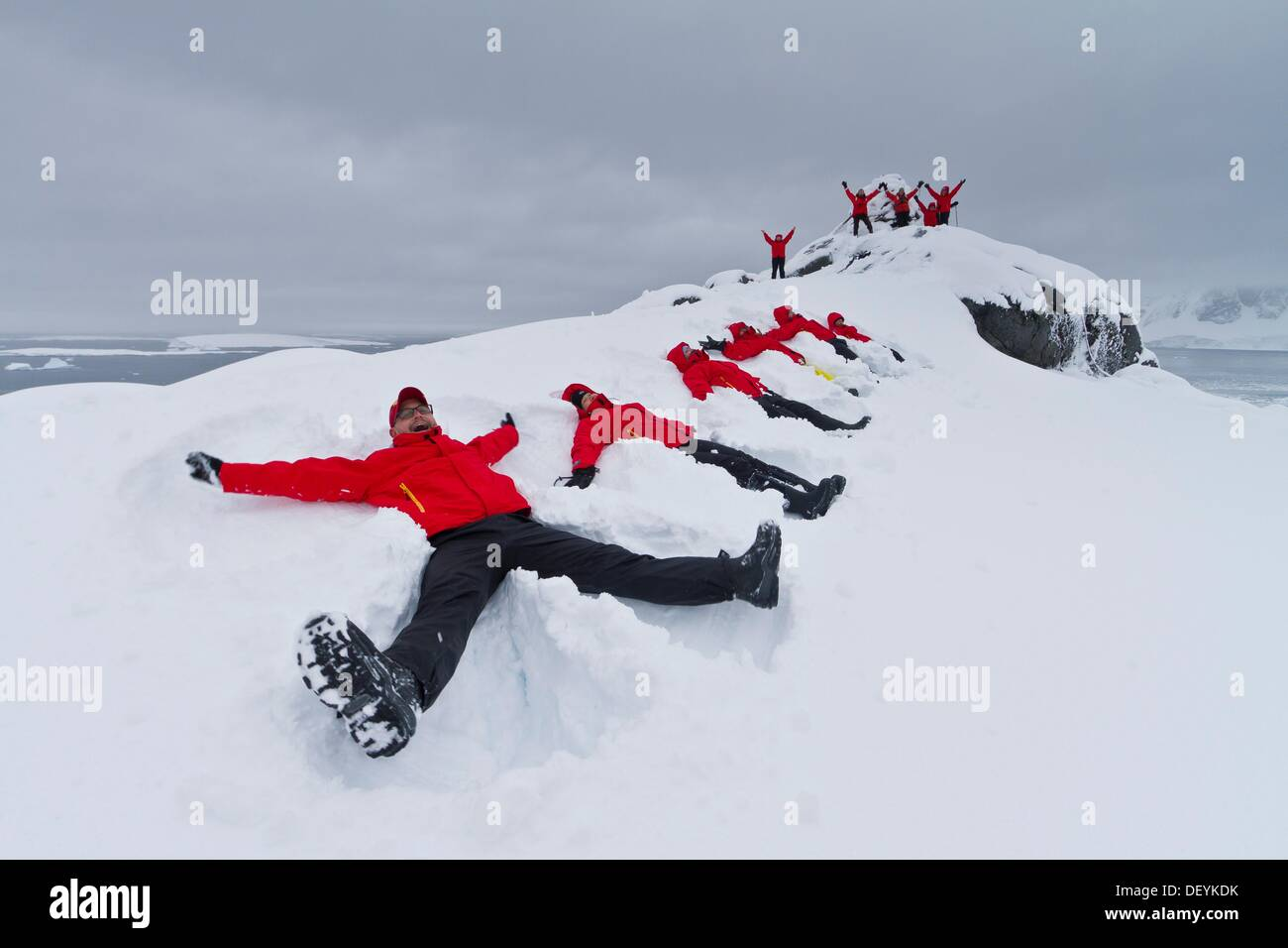 Guests from the Lindblad Expedition ship National Geographic Explorer enjoy making snow angels in fresh snow on Booth Island, - Stock Image