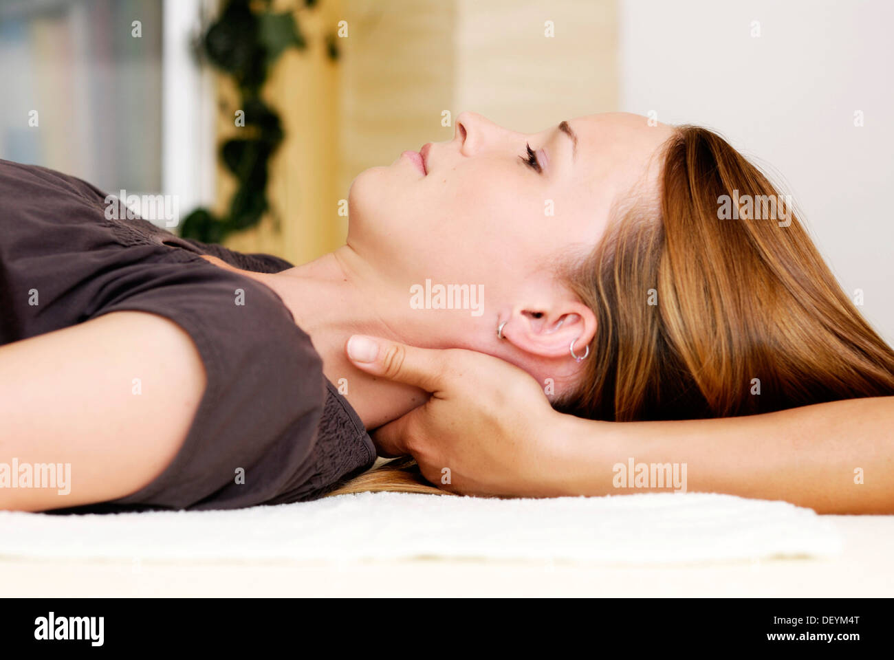 Young woman receiving cranio-sacral therapy in a natural healing practice - Stock Image