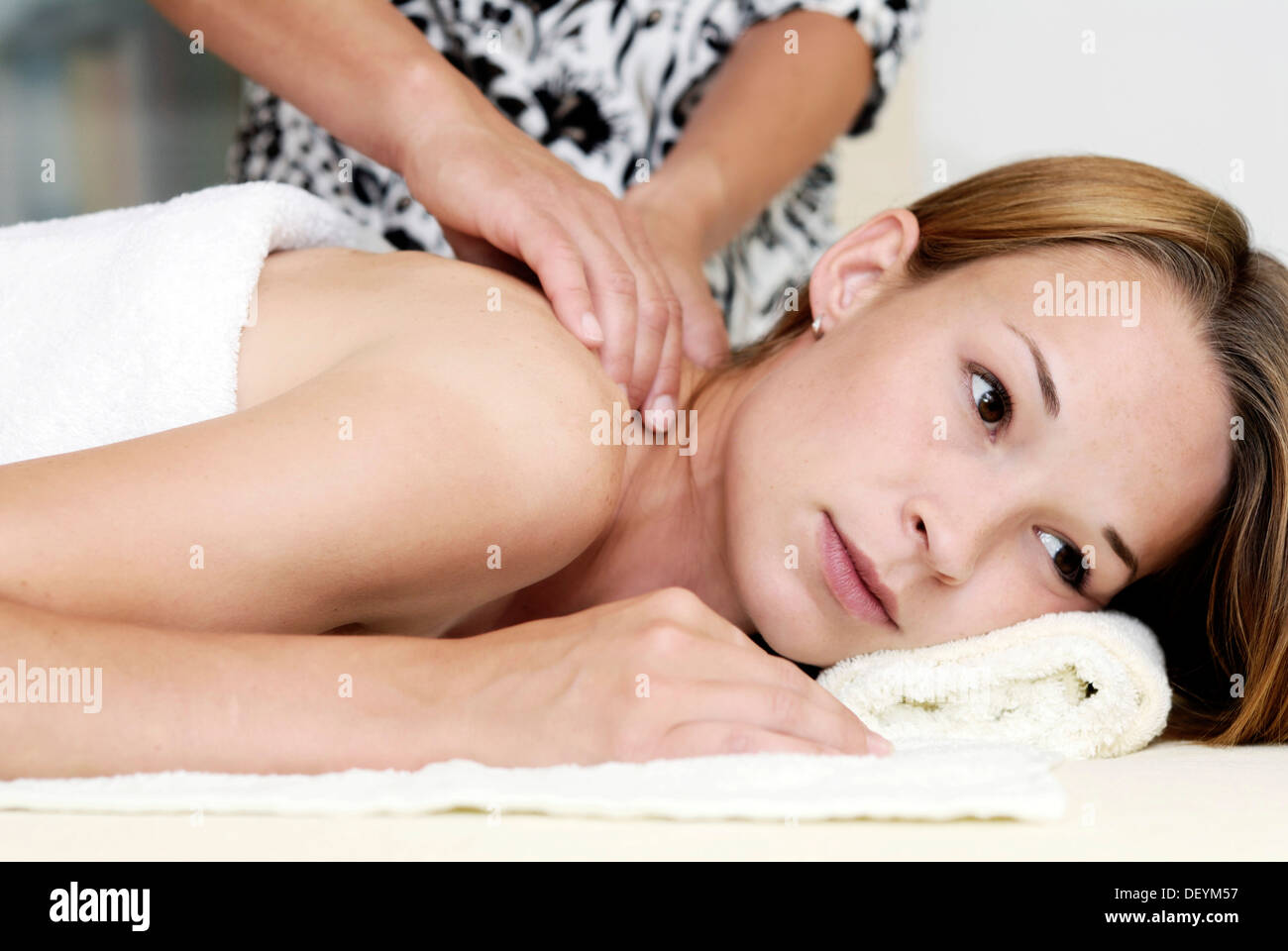 Young woman receiving massage therapy - Stock Image