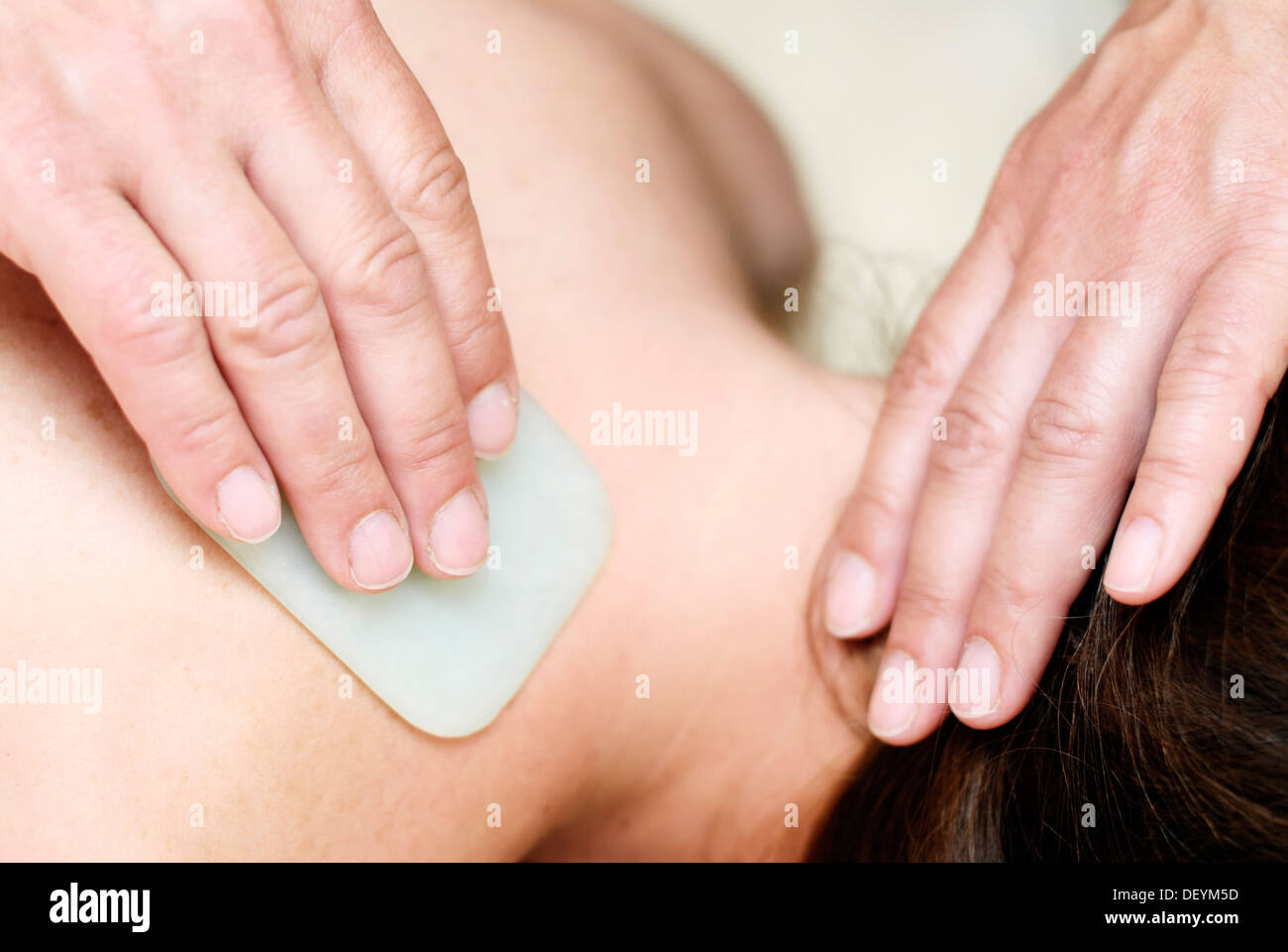 Young woman receiving Gua Sha therapy in a natural healing practice - Stock Image
