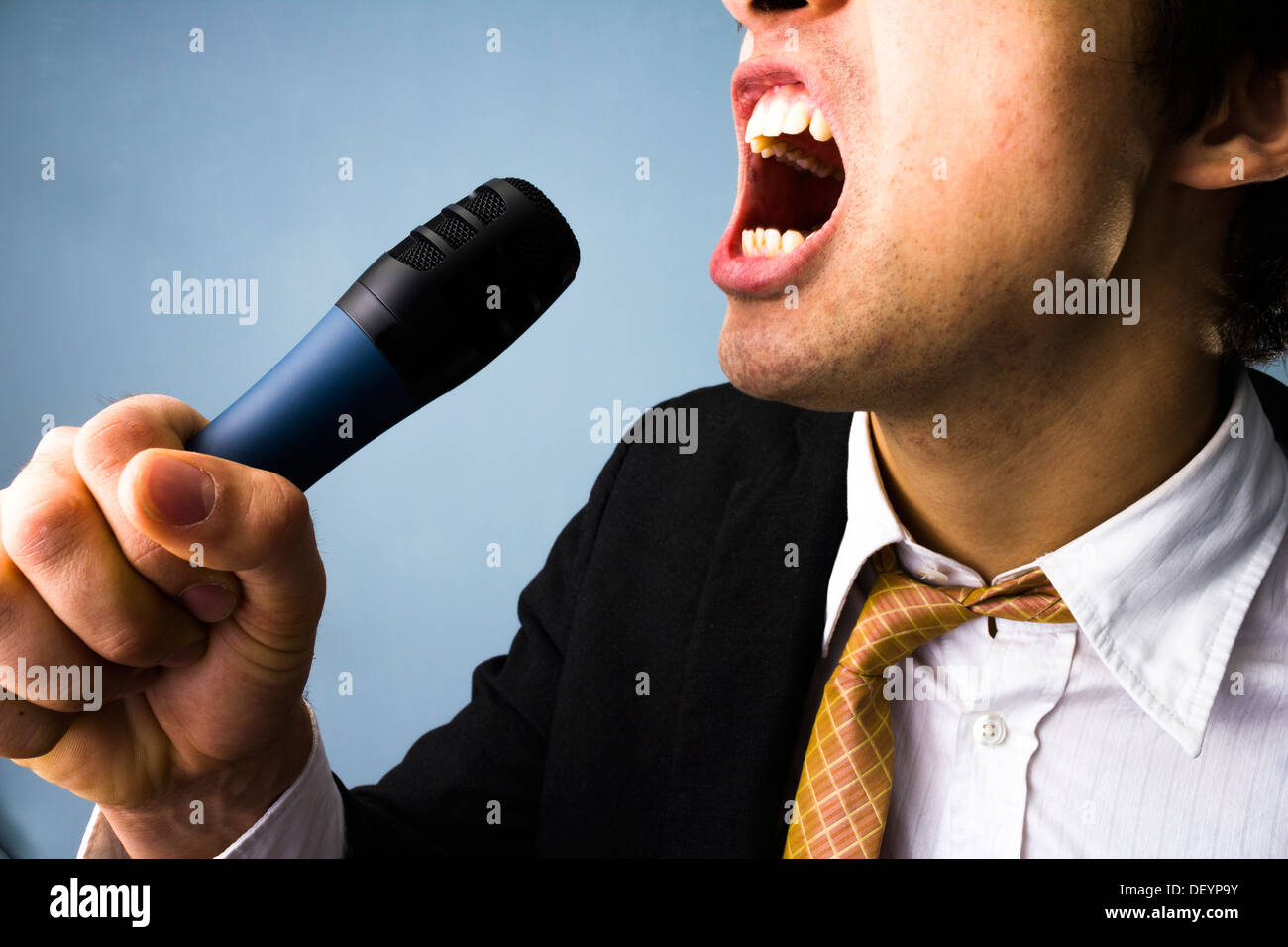 Close up on a young businessman's face as he is singing karaoke - Stock Image