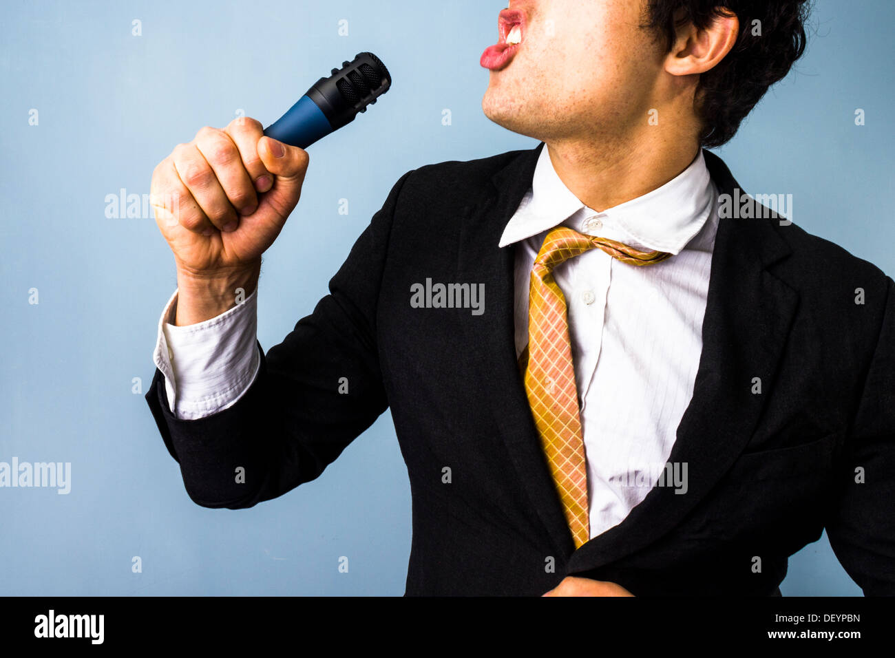 Young businessman with microphone is singing karaoke - Stock Image