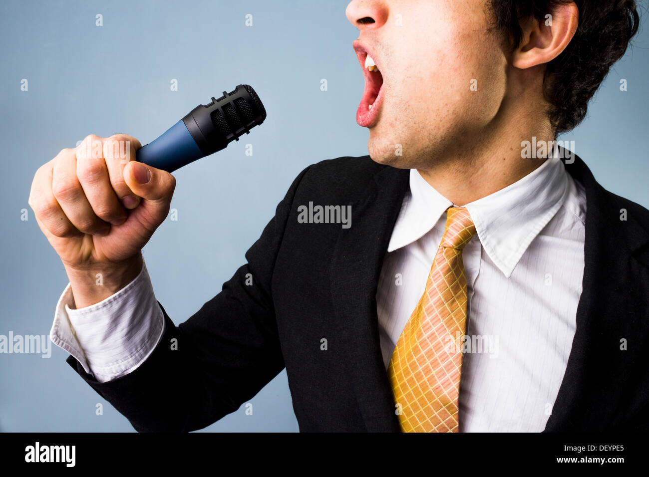 Young multi racial businessman is singing karaoke - Stock Image