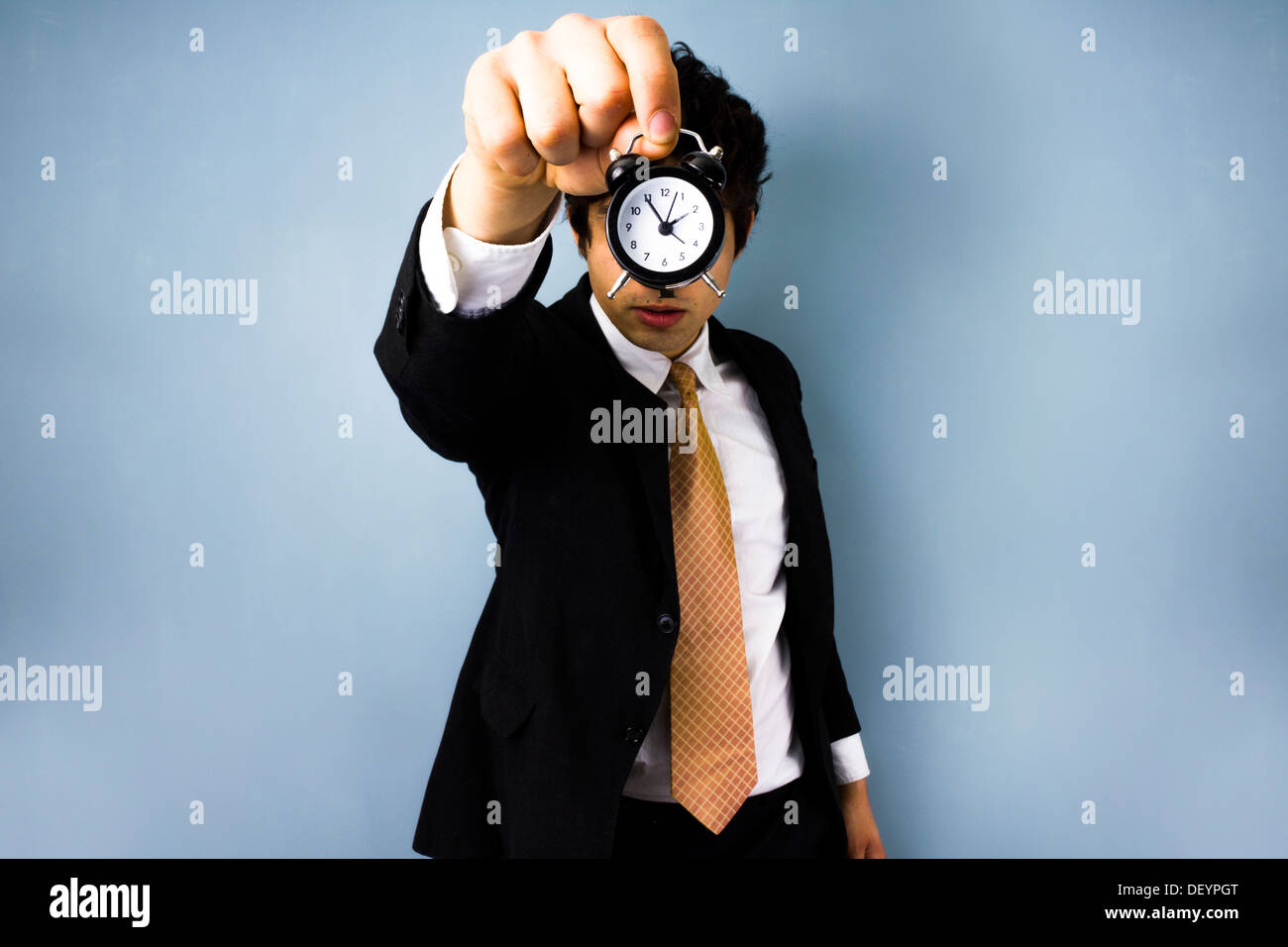 Young business man holding an alarm clock in front of his face - Stock Image