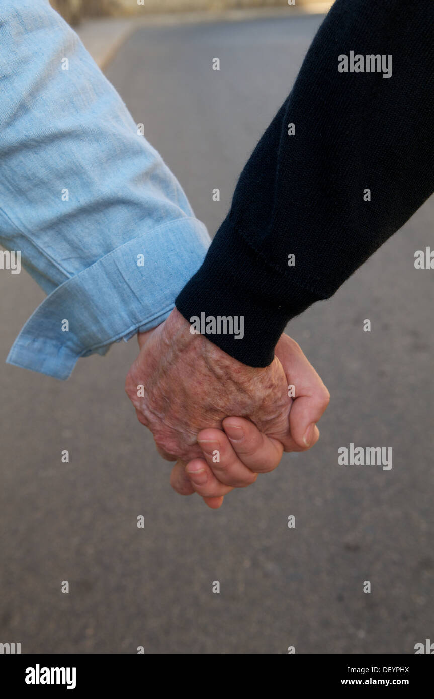 Two hands held, one old one young. - Stock Image