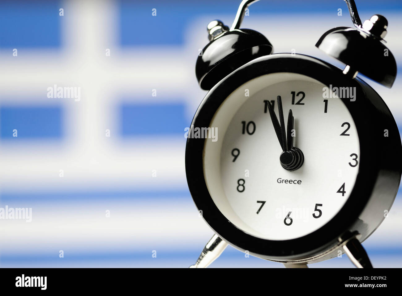 Five to twelve on an alarm clock display in front of Greek national flag, symbolic image, threat of impending national - Stock Image