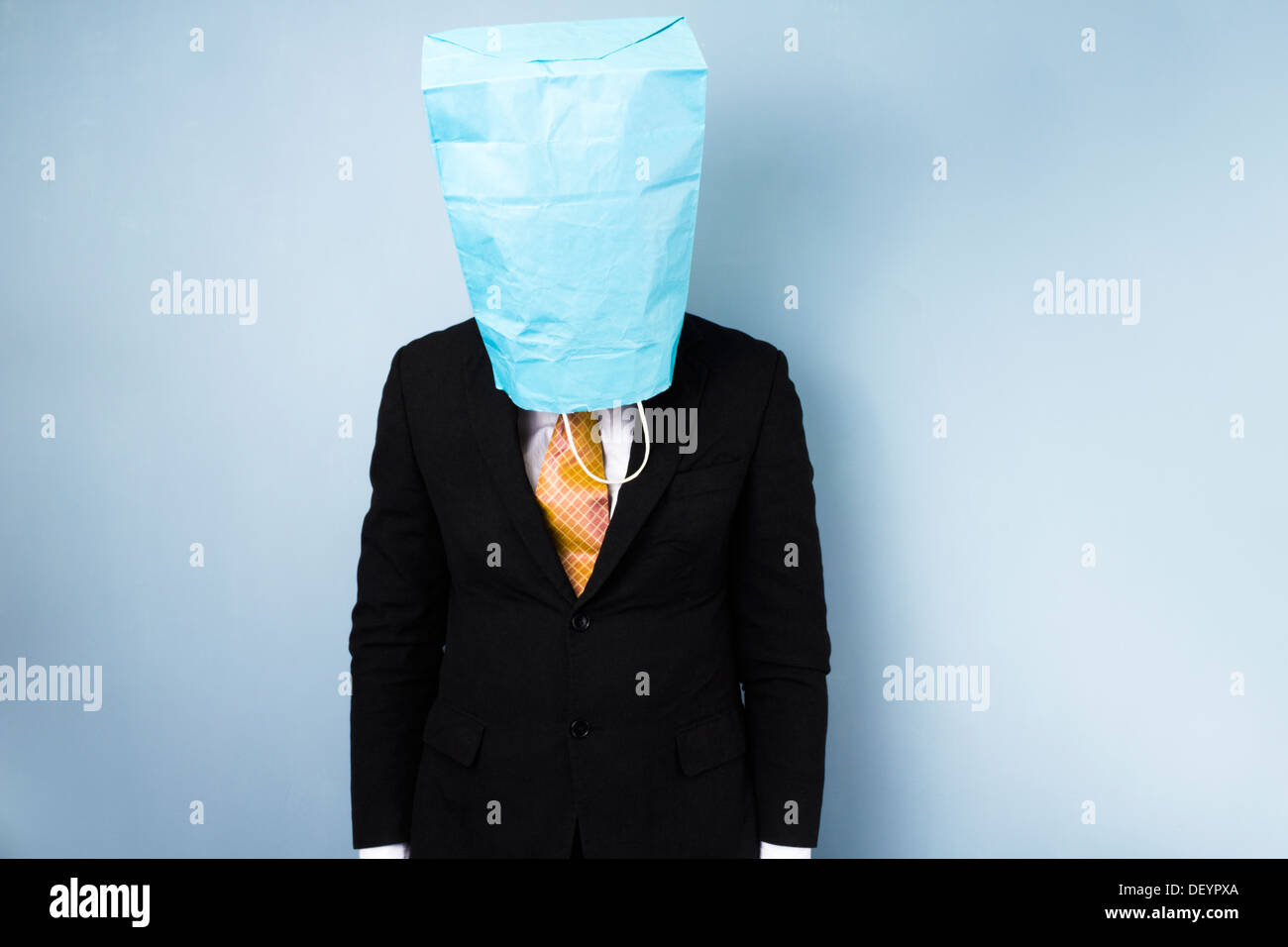Ashamed businessman is hiding his face inside a paper bag - Stock Image