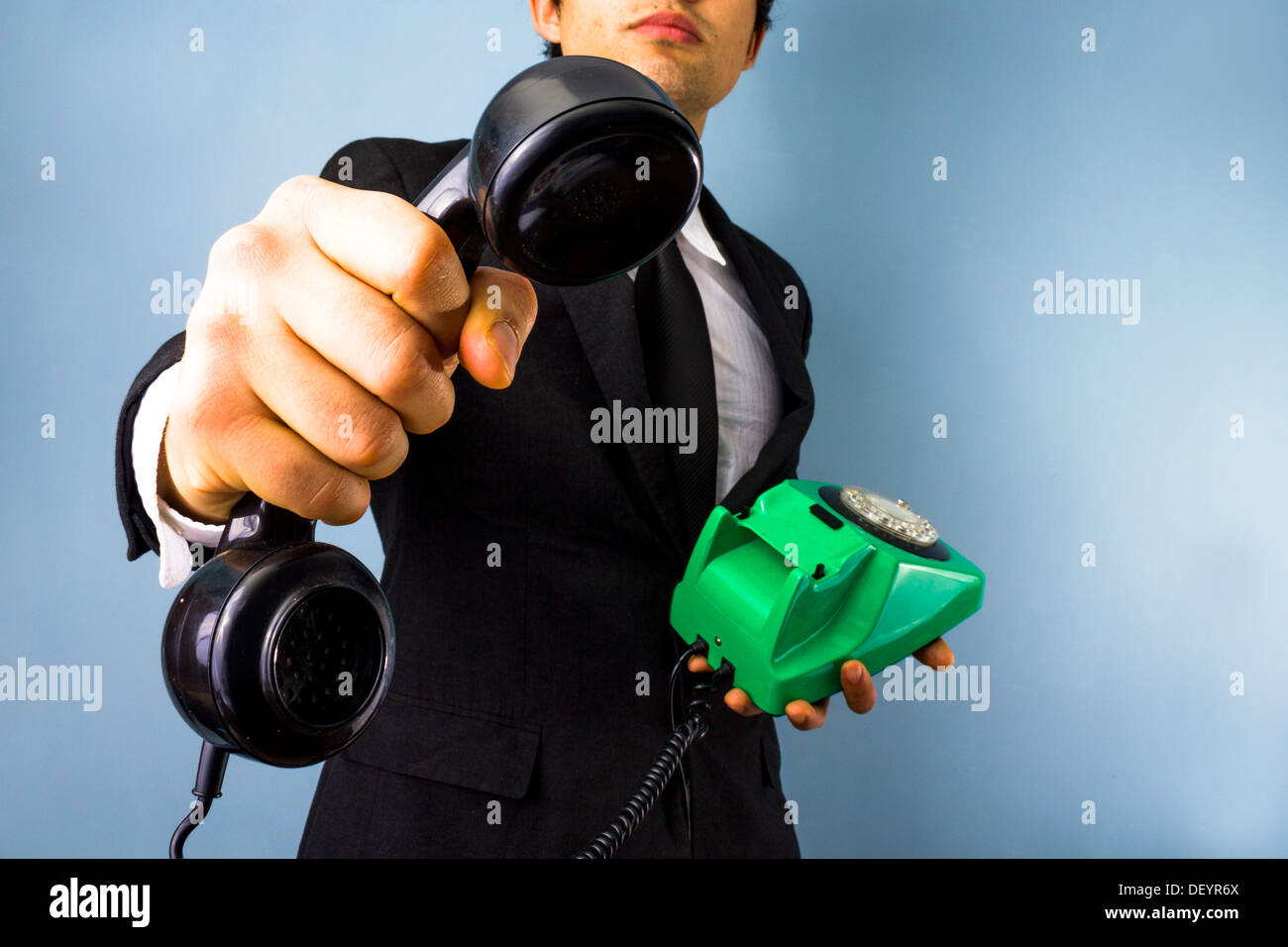 Young businessman handing over a phone - Stock Image